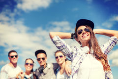 Adolescente con los auriculares y los amigos afuera Fotos de archivo libres de regalías