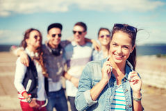 Adolescente con los auriculares y los amigos afuera Fotografía de archivo libre de regalías