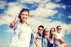Adolescente con los auriculares y los amigos afuera Fotografía de archivo