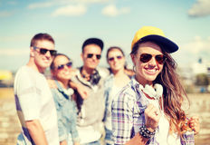 Adolescente con los auriculares y los amigos afuera Imagen de archivo libre de regalías