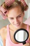 Adolescente con los bigudíes del espejo y de pelo Fotografía de archivo libre de regalías