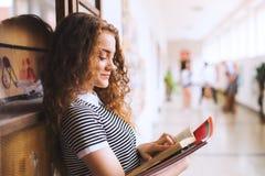 Adolescente con los cuadernos en pasillo de la High School secundaria durante rotura Imágenes de archivo libres de regalías