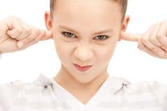 Adolescente con los fingeres en oídos Imagen de archivo libre de regalías