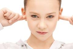 Adolescente con los fingeres en oídos Fotos de archivo libres de regalías
