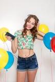 Adolescente con los globos del helio sobre fondo gris Fotos de archivo libres de regalías
