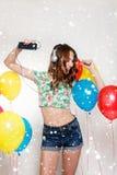 Adolescente con los globos del helio sobre fondo gris Foto de archivo