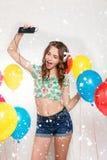 Adolescente con los globos del helio sobre fondo gris Fotos de archivo