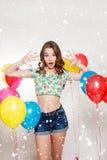 Adolescente con los globos del helio sobre fondo gris Fotografía de archivo libre de regalías