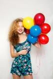 Adolescente con los globos del helio sobre fondo gris Imagen de archivo