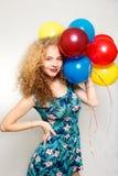 Adolescente con los globos del helio sobre fondo gris Foto de archivo libre de regalías