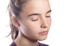Adolescente con los ojos cerrados, aislados en blanco Imagen de archivo
