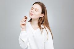 Adolescente con los ojos cerrados comiendo el chocolate Fotografía de archivo libre de regalías