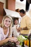 Adolescente con los padres en la sonrisa de la cocina Imagen de archivo libre de regalías