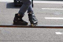 Adolescente con los pcteres de ruedas que realizan un truco en una media rampa del tubo Imagen de archivo libre de regalías