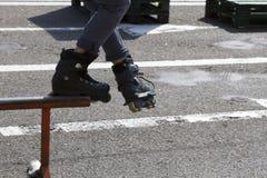 Adolescente con los pcteres de ruedas que realizan un truco en una media rampa del tubo Fotografía de archivo