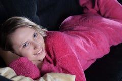 Adolescente con los pijamas en el sofá Fotografía de archivo libre de regalías