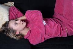 Adolescente con los pijamas en el sofá Imagenes de archivo