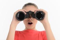 Adolescente con los prismáticos. Mirada adolescente emocionada a través del BI Imagenes de archivo