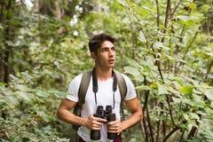 Adolescente con los prismáticos que caminan en vacaciones de verano del bosque Fotografía de archivo libre de regalías