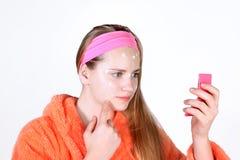Adolescente con los problemas de piel que aplican el ungüento Medicación del acné Imagenes de archivo