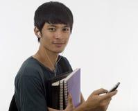 Adolescente con musica ed i libri Fotografia Stock