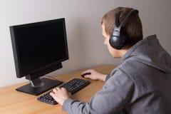 Adolescente con el ordenador y los auriculares Imagen de archivo libre de regalías