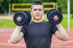 Adolescente con pesas de gimnasia en la tierra de deportes Imagen de archivo