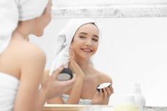 Adolescente con problema del acné usando la crema Imagen de archivo libre de regalías