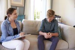 Adolescente con problema que habla con el consejero en casa Imagen de archivo