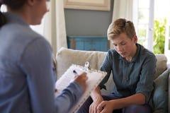 Adolescente con problema que habla con el consejero en casa Foto de archivo libre de regalías
