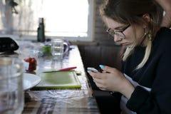 Adolescente con smartphone en cocina fotos de archivo