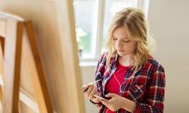 Adolescente con smartphone en el estudio de la escuela de arte Imagen de archivo libre de regalías