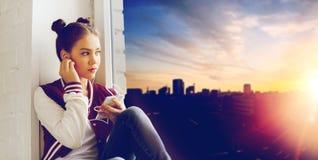 Adolescente con smartphone y los auriculares Foto de archivo libre de regalías