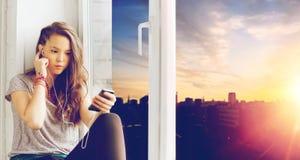 Adolescente con smartphone y los auriculares Imágenes de archivo libres de regalías