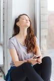 Adolescente con smartphone y los auriculares Fotografía de archivo