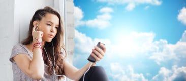 Adolescente con smartphone y los auriculares Imagen de archivo libre de regalías
