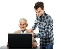 Adolescente con su abuelo en el ordenador portátil fotos de archivo libres de regalías