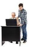Adolescente con su abuelo en el ordenador portátil Fotografía de archivo