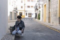 Adolescente con su cámara de la foto que saluda un gato de la calle Foto de archivo
