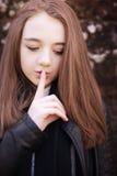 Adolescente con su finger a sus labios para el silencio Fotos de archivo libres de regalías
