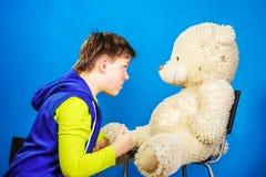 Adolescente con su juguete viejo del peluche-oso Fotografía de archivo libre de regalías