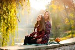 Adolescente con su madre que se sienta cerca del lago Fotos de archivo