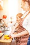 Adolescente con su mamá que se divierte en cocinar Fotos de archivo