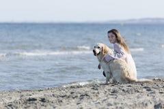 Adolescente con su perro en una playa Imágenes de archivo libres de regalías