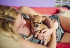 Adolescente con su perro que pone en cama Foto de archivo