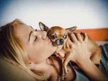 Adolescente con su perro que pone en cama Fotografía de archivo