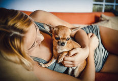 Adolescente con su perro que pone en cama Fotos de archivo