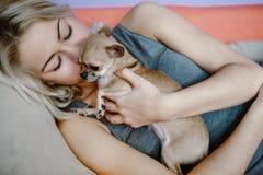 Adolescente con su perro que pone en cama Fotografía de archivo libre de regalías