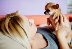 Adolescente con su perro que pone en cama Fotos de archivo libres de regalías