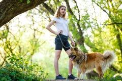Adolescente con su perro que se coloca en rastro Fotografía de archivo